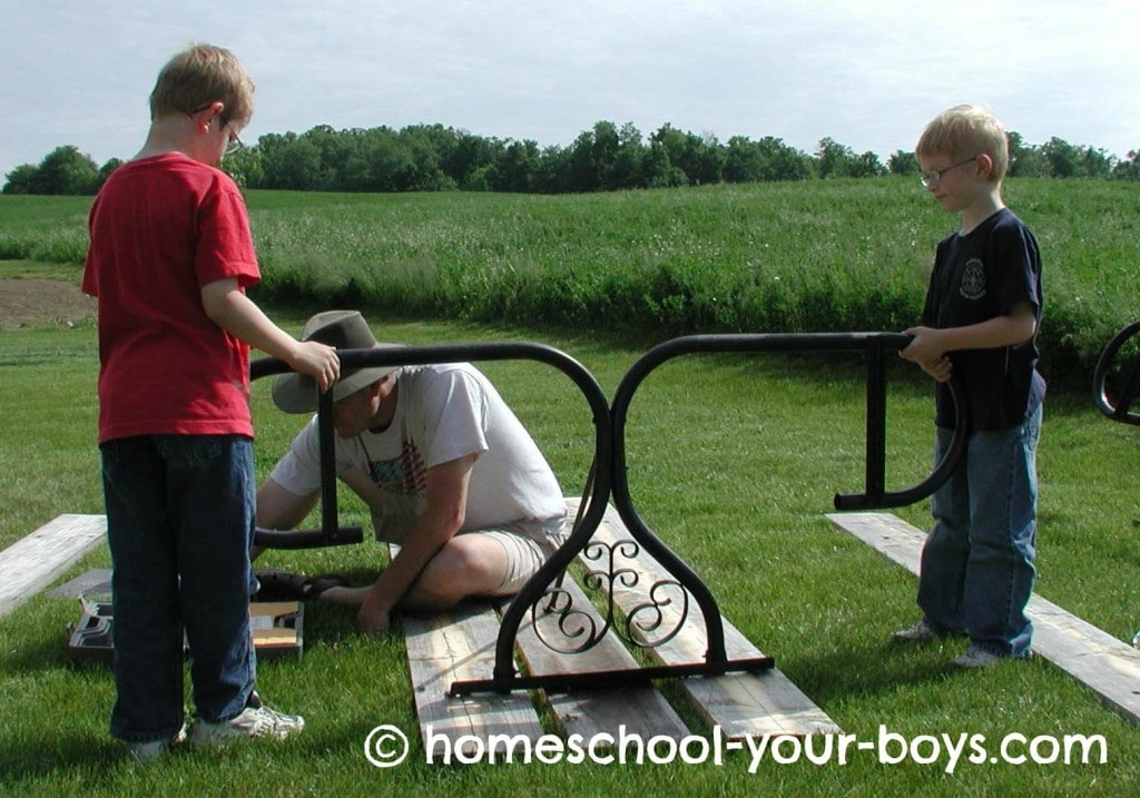 Dad and sons repairing a picnic table