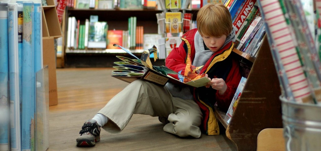 Boy reading a pop-up book in a bookstore