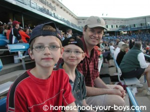 Dad with two sons at a baseball game