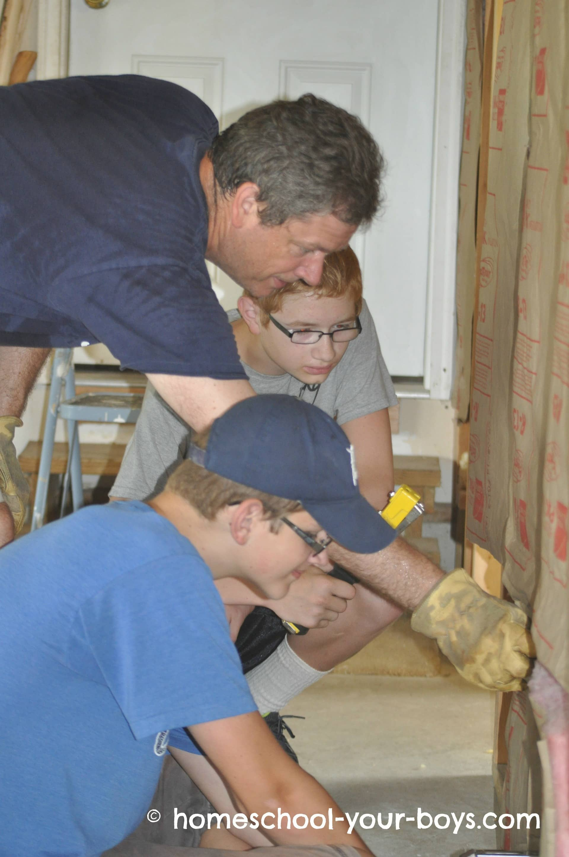 Dad showing his sons how to hang insulation
